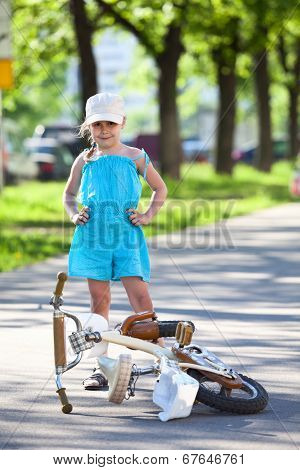 Girl Standing Near A Bicycle Which Laying On Pavement