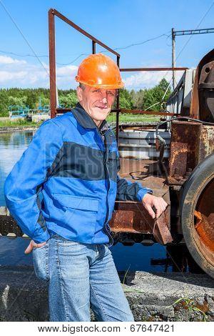 Senior Man Mechanist Standing Near Sewage Treatment Plant