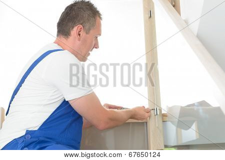 Carpenter working with screwdriver on stairs