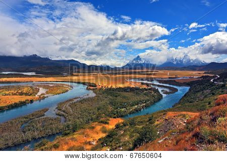 Glen Serrano. Meandering river bed of yellow autumn coast. Valley surrounded by snow-capped mountains