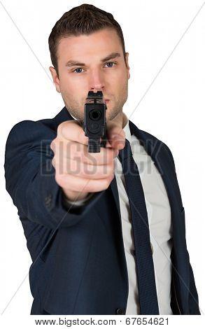 Serious businessman pointing a gun on white background