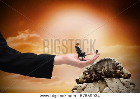 Businesswoman sitting on swivel chair with feet up in large hand against large rock overlooking orange sky