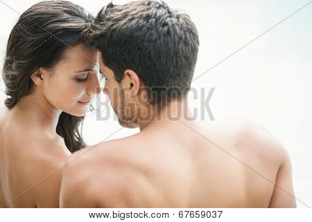 Attractive couple sitting poolside smiling on a sunny day