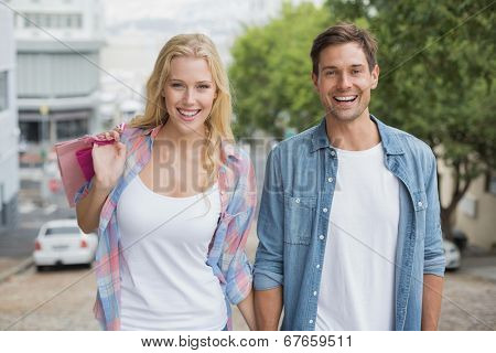 Hip young couple on shopping trip walking uphill on a sunny day in the city
