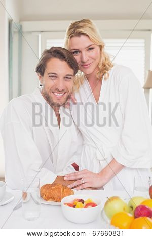 Couple smiling at camera in their bathrobes at home in the living room