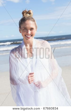 Pretty blonde wrapped in white shawl on the beach on a bright day