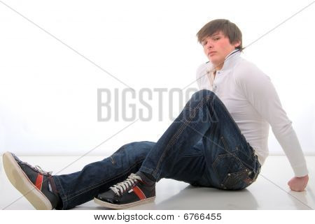 Jeans Young Mann Sitting On White Floor. Studio Shoot Over White Background.