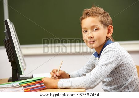 Portrait of smart lad by the desk looking at camera