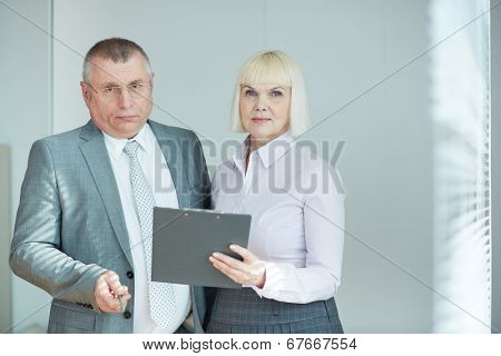 Confident mature co-workers looking at camera