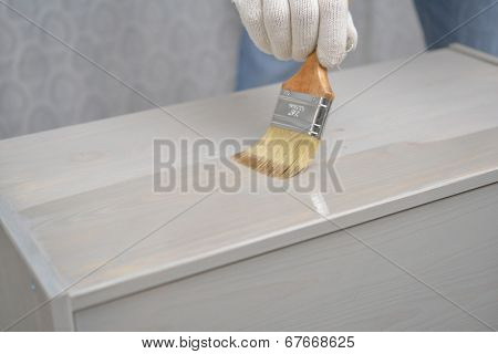 Contractor varnishing the wooden chest