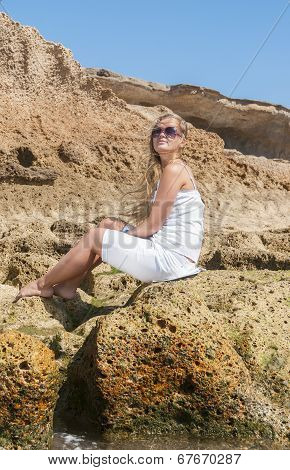 Blondy girl in white dress with sunglasses on the beach