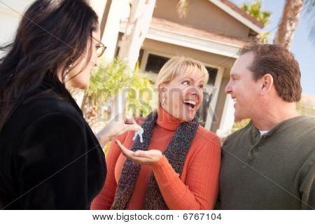 Hispanos mujer agente inmobiliario entrega las llaves a pareja emocionado