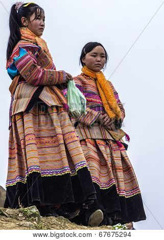 Two Young Hmong Women Show And Wait At Sunday Market.