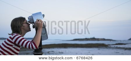 Woman Looking Through Telescope At Beach