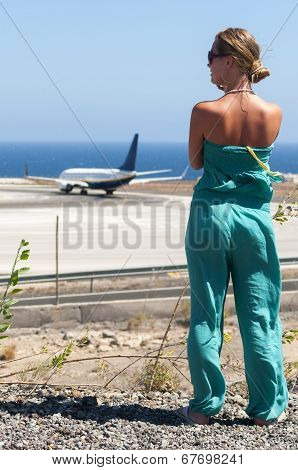 Beautiful blondy with long hair looking at airplane