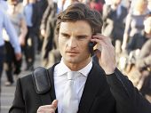 stock photo of commutator  - Male commuter in crowd using phone - JPG