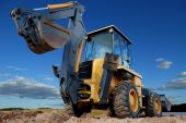 foto of earth-mover  - Excavator Loader with raised backhoe standing over cloudscape sky - JPG