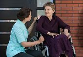 stock photo of compassion  - Nurse and elderly lady in front of house - JPG