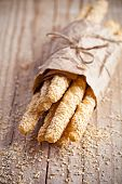 image of sesame seed  - bread sticks grissini with sesame seeds in craft pack on rustic wooden background - JPG
