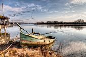 stock photo of marshlands  - landscape at morning with abandoned boat and fishing shacks in the river of Ravenna Italy - JPG