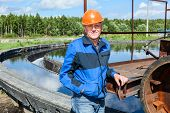 stock photo of sewage  - Senior workman with orange hardhat in sewage treatment plant - JPG