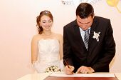 picture of appendicitis  - The groom appends the signature in the document of registration of marriage - JPG