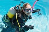 stock photo of oxygen mask  - Smiling woman on scuba training in swimming pool on a sunny day - JPG