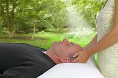 picture of wicca  - Female healer giving healing to male supine client outdoors with a woodland background - JPG