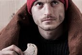 image of beggar  - Homeless and hungry man eating a piece of bread - JPG