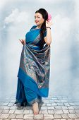 stock photo of vedic  - Caucasian mature woman posing in blue sari on sky background