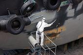 image of shipbuilding  - man spray painting hood of ship grey in dock - JPG