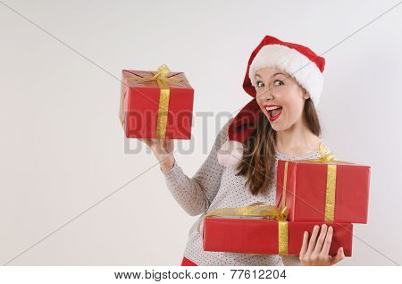 Cute Exciting Young Woman With Present Boxes In Santa Hat On White Background