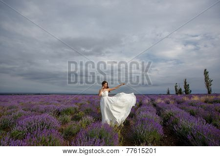 Beautiful bride walks through a field of lavender.