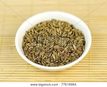 Cumin Seeds In Bowl Against Wooden Background