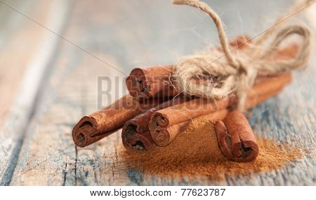Sticks And Powder Aroma Cinnamon On Old Wooden Background