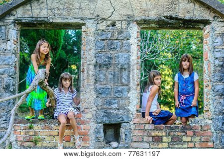 Four little girls playing around old house ruins