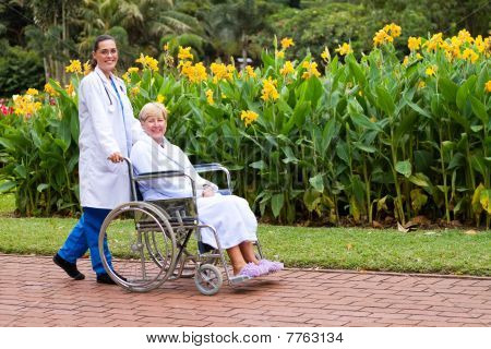 nurse pushing happy wheelchair patient