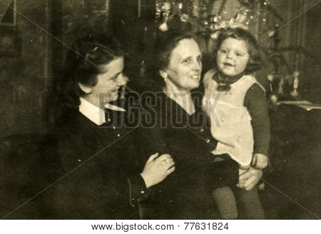 GERMANY, CIRCA 1940s: Vintage photo of grandmother, mother and little girl in front of Christmas tree