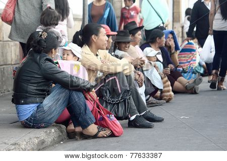 women sit on bordure, the street in Sucre
