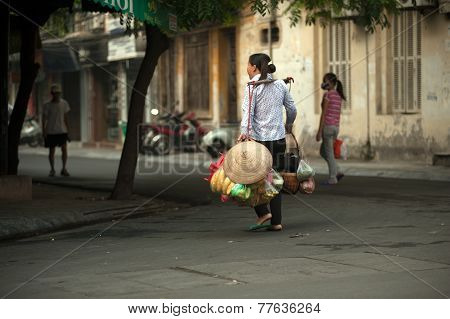 Woman Carrying Commodity On Street In Hanoi,vietnam.