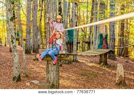 Little girls on zip line in adventure park