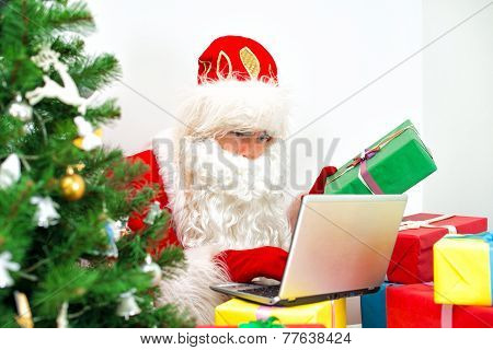 Santa Claus Checking Wishlist At His Workshop.