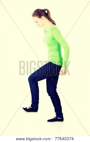 Attractive young woman with one leg up. Side view. Isolated on white.