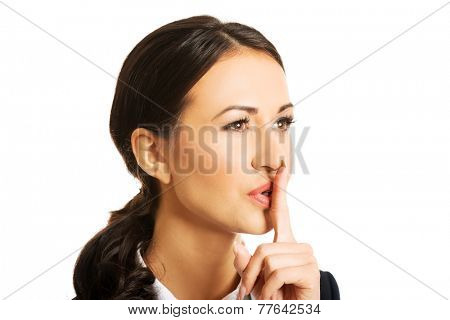 Portrait of businesswoman making silent sign.