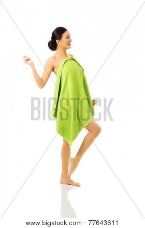 Full length woman wrapped in towel with leg up.