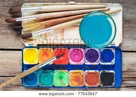 Set Of Watercolor Paints, Art Brushes And Glass Of Water On Old Wooden Table.