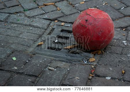 Old Soccer Ball In Gutter