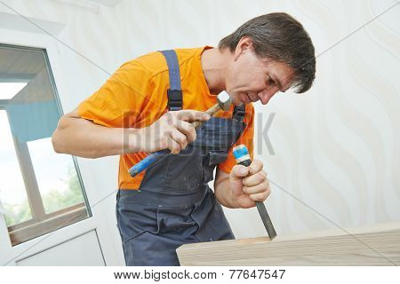 Male carpenter at interior wood door lock installation working with hammer and chisel