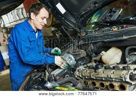 auto mechanic repairing automobile car engine turbine at maintenance repair service station garage
