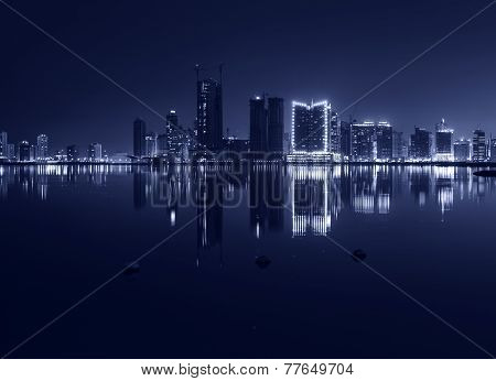 Night Modern City Skyline With Shining Lights And Reflection